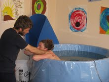 Laboring woman in a birthing tub being massaged by her partner.