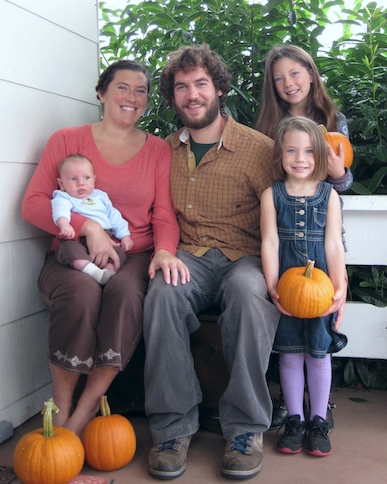 Smiling family of five posing with orange pumpkins.