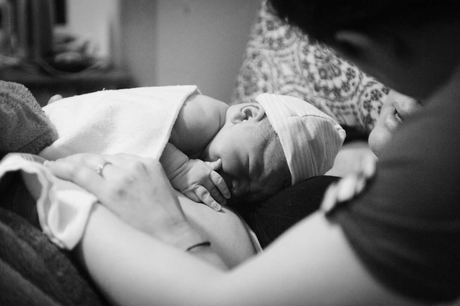 Sleeping newborn with hat and blanket resting on mother's stomach.