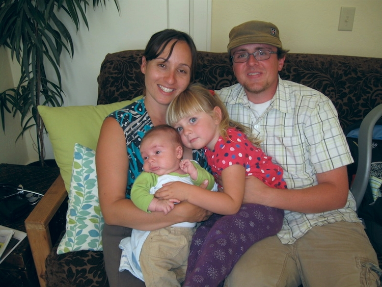 A happy family sitting on a couch with a young girl and an infant sitting in the laps of the parents.