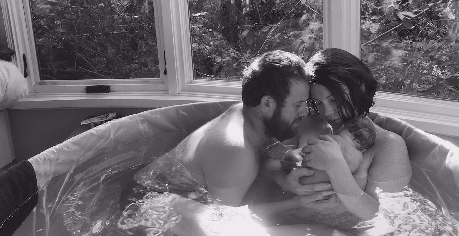 Black and white photo of a mother and father in a birthing tub with a newborn baby.