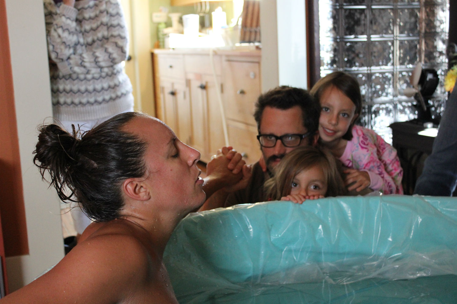 Mother in labor in a birthing tub with daughters and husband kneeling at the side of the tub providing support.